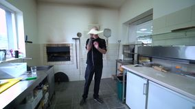 Ein junger Pizzahersteller bereitet Pizza in der Küche des Restaurants zu E Langsame Bewegung stock video