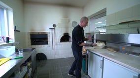 Ein junger Pizzahersteller bereitet Pizza in der Küche des Restaurants zu E Langsame Bewegung stock footage