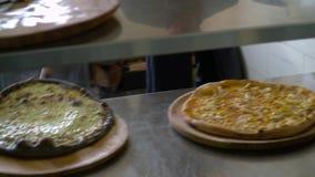 Ein junger Pizzahersteller bereitet Pizza in der Küche des Restaurants zu Der Koch nimmt die bereite Pizza vom erhitzten heraus stock footage