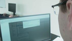 Ein junger Programmierer zerhackt das Programm Die Kamera summt herein durch die Gläser zum Monitor laut stock video
