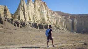 Ein junger Reisender geht entlang einen Weg in einem Berggebiet stock video