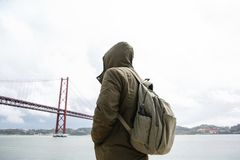 Ein junger Reisender oder ein Tourist mit einem Rucksack auf der Ufergegend in Lissabon in Portugal nahe bei dem 25. von April Br Lizenzfreie Stockfotografie