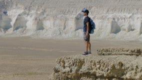 Ein junger Reisender steht am Rand der Klippe und schaut herum Stockbild