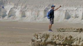 Ein junger Reisender steht am Rand einer Klippe und macht ein selfie Stockfotos
