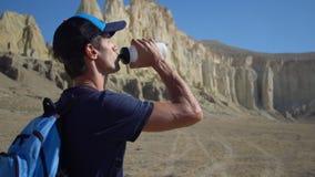 Ein junger Reisender trinkt Wasser gegen die Felsen Lizenzfreies Stockbild