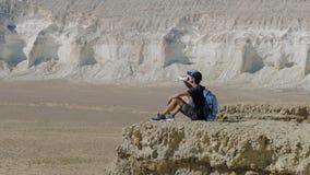 Ein junger Reisender trinkt Wasser gegen die Felsen Lizenzfreie Stockfotografie