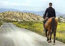 Ein junger Reiter, der sein Pferd auf eine Gebirgsstraße reitet stockbild
