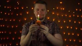 Ein junger rot-bärtiger Mann, der heraus eine Kerze auf einem Kuchen nahe bei den gelben Lichtern durchbrennt stock video footage