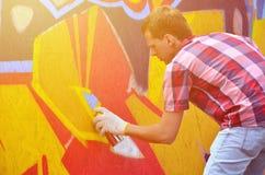 Ein junger rothaariger Graffitikünstler malt neuen Graffiti auf Lizenzfreie Stockbilder