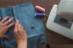Ein junger Schneider, eine Näherin umreißt die Änderungen im Muster vonseiten des geschnittenen blauen Geweberockes Ist in der Nä stockbilder