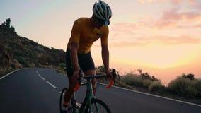 Ein junger Sportmann fährt Fahrrad auf einen Gebirgsserpentin in einer gelben T-Shirt Sturzhelm- und Sportausrüstung, die betrach stock footage