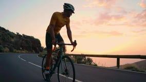 Ein junger Sportmann reitet ein Fahrrad auf einen Gebirgsserpentin und Blicke an der Kamera in einem gelben T-Shirt und im Sport stock video
