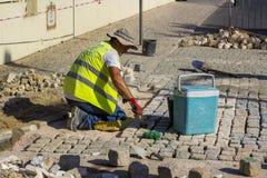 Ein junger Steinmaurer, der Kopfsteine in Albuferia Portugal legt lizenzfreie stockbilder