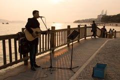 Ein junger Straßenmusiker, der entlang dem Strand in Xiamen-Stadt, China singt Stockbild