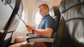 Ein junger Tourist arbeitet im Flugzeug mit der Tablette, bevor er geht stockbilder