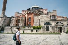 Ein junger Tourist steht auf dem Quadrat nahe der Moschee Der Kerl wird durch die Größe und die Schönheit der Moschee beeindruckt Lizenzfreie Stockfotos