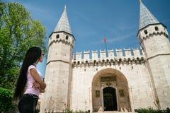 Ein junger Tourist steht auf dem Quadrat nahe der Moschee oder dem Turm Das Mädchen wird durch Schönheit der Moschee beeindruckt Lizenzfreie Stockfotografie