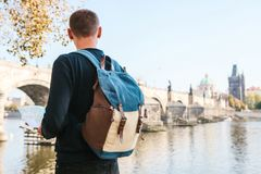 Ein junger touristischer Mann mit einem Rucksack, der nahe bei dem Fluss die Moldau in Prag steht, betrachtet die Karte und bewun lizenzfreie stockfotos