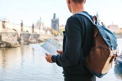 Ein junger touristischer Mann mit einem Rucksack, der nahe bei dem Fluss die Moldau in Prag steht, betrachtet die Karte und bewun lizenzfreies stockfoto