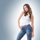 Ein junger und reizvoller Brunette, der in den stilvollen Jeans aufwirft Stockfotografie