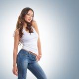 Ein junger und reizvoller Brunette, der in den stilvollen Jeans aufwirft Stockbild