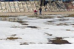 Ein junger Vater mit einem Spaziergänger und einem Los Schnee Lizenzfreies Stockfoto