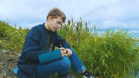 Ein junger Verfasser sitzt auf der Flussbank stock video