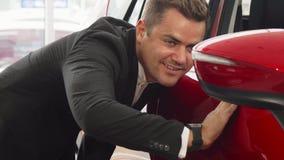 Ein junger Verkäufer überprüft die Integrität des Autos stockfoto