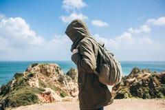Ein junger Wanderer mit einem Rucksack geht entlang die Atlantikküste in Portugal lizenzfreies stockbild