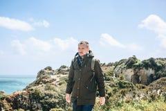 Ein junger Wanderer mit einem Rucksack geht entlang die Atlantikküste in Portugal lizenzfreie stockfotos