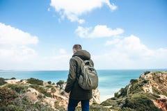 Ein junger Wanderer mit einem Rucksack geht entlang die Atlantikküste in Portugal lizenzfreie stockbilder