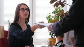 Ein junger weiblicher Hauptgeschäftsführer, der ein Klemmbrett mit Anweisung zu ihrer Unterordnung gibt