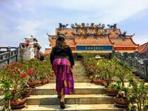 Ein junger weiblicher Reisender, der herauf die Schritte hin zu Guan Im Sutham Temple in Kanchanaburi, Thailand geht stockbild