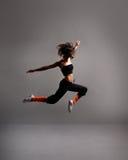 Ein junger weiblicher Tänzer führt einen Sprung durch Stockbilder