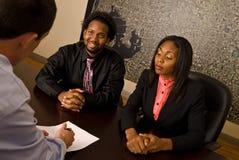 Junge Afroamerikanerpaare ungefähr, zum der Papiere zu unterzeichnen Stockfotos