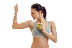 Ein junges athletisches Mädchen in der grauen Spitze mit einem Maßband an Hand hält Apple und blickt in Richtung Stockbilder