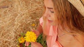 Ein junges attraktives Mädchen in einem Strohhut sitzt auf dem Heu und hält eine gelbe Blume in ihrer Hand, und schnüffelt sie da stock video