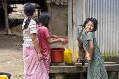 Ein junges birmanisches Mädchen pumpt Wasser in einem Flüchtlingslager in Thailand stockfotografie