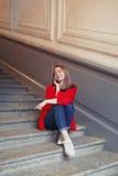 Ein junges blondes Mädchen, das am Telefon sitzt auf den Schritten, eingewickelt in einer roten Decke spricht Sie ist glücklich u Stockfoto