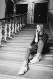 Ein junges blondes Mädchen, das am Telefon sitzt auf den Schritten spricht Sie ist glücklich und Lächeln Stockbild