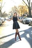 Ein junges blondes Mädchen mit Kleid und Stiefel, die in der Mitte der Straße stehen Stockbild