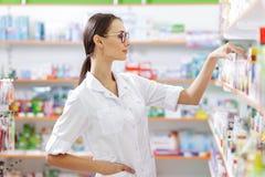 Ein junges dünnes braunhaariges Mädchen mit den Gläsern, gekleidet in einem Laborkittel, nimmt etwas Medizin vom Regal in einer A lizenzfreie stockbilder