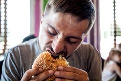 Ein junges Fleisch fressendes ein Burger stockfotografie