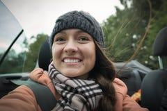 Ein junges frohes Mädchen reist in das Cabrioletauto stockbilder