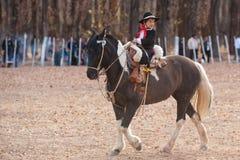 Ein junges Gaucho, das ein Pferd in der Ausstellung reitet Stockbilder