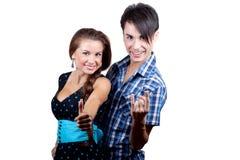Ein junges glückliches Paar, das sich Daumen zeigt. Lizenzfreies Stockfoto