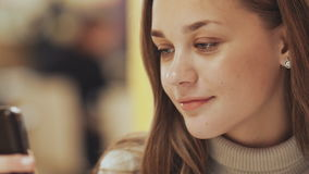 Ein junges hübsches Mädchen liest und schreibt Mitteilungen am Telefon, das in ein Café am Tisch sitzt Nahaufnahme stock video footage