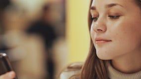 Ein junges hübsches Mädchen liest und schreibt Mitteilungen am Telefon, das in ein Café am Tisch sitzt Nahaufnahme stock footage