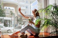 Ein junges hübsches Mädchen mit dem langen Haar, gekleidet in der zufälligen Kleidung, sitzt auf einem Fensterbrett und nimmt ein lizenzfreies stockbild