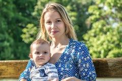 Ein junges hübsches motherr mit einem kleinen Babysohn im Freien auf einer Bank Stockbild